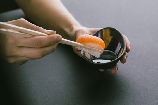 Sushi dunking in sauce