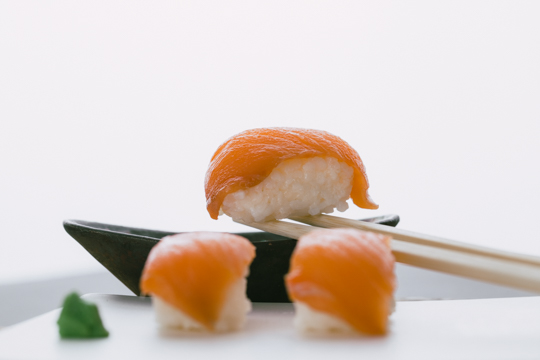 Sushi hovering over sauce